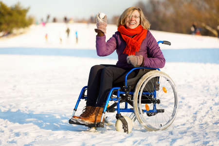 happy adult woman wearing winter clothes on sitting on wheelchair in the snow throwing snowball Stock Photo