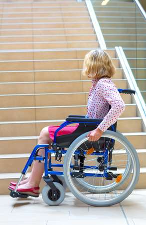 woman on wheelchair standing before stairs looking up for help Stock Photo