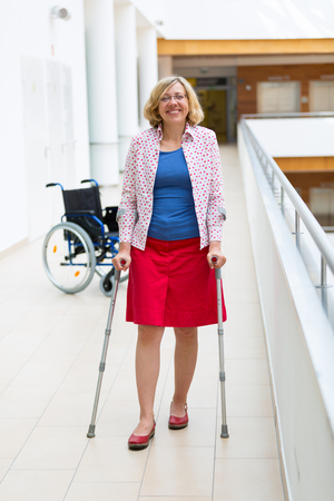 woman practicing walking on crutches in the hospital, wheelchair in the background