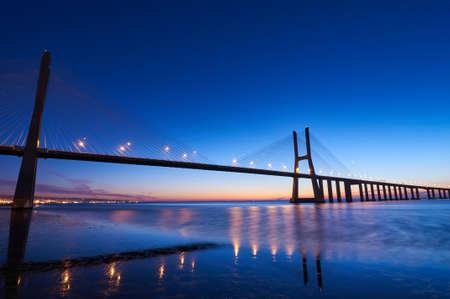 Ujęcie z długim czasem ekspozycji mostu Vasco da Gama w Lizbonie przed wschodem słońca