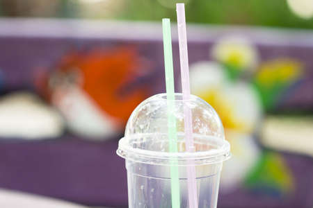 Water glass with a green and Pink  straw