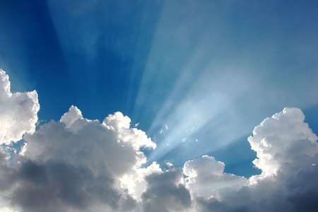 colorful blue sky with tiny clouds and sun rays