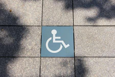 Handicap sign on tile floor, disable symbol