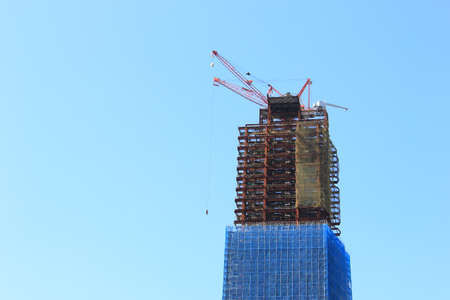 Crane and building under construction site on sky background Imagens