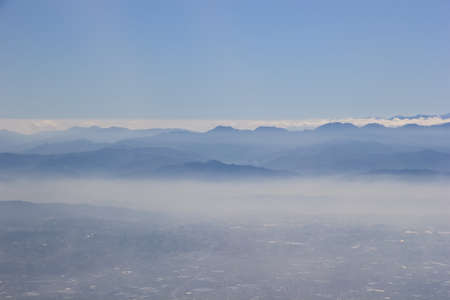 City and mountain in the fog, through from window airplane