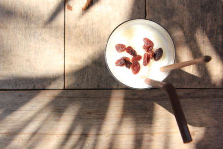 Delicious smoothie with rum raisin on wooden table  and coconut tree shadow Imagens