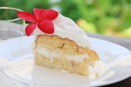 Delicious coconut cake with plumeria ruba flower on white plate