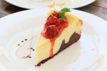 gateau: slice of cheesecake with cherry sauce and ixora flower on white plate