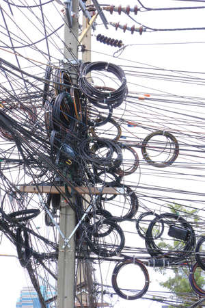 Chaos messy tangle of electric cable on post Imagens