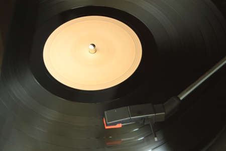 A vinyl record being played on a dusty old turntable photo