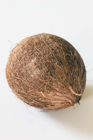copra: A whole coconut displayed on a white background Stock Photo