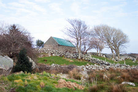 bleak: An old shed in a bleak landscape with stone walls Stock Photo