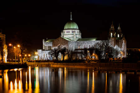 A view of Galway Cathedral and it's reflection along with surrounding lights in the River Corrib