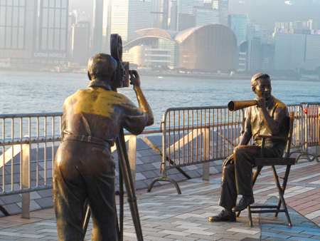 film director: Victoria Harbour, Hong Kong - February 2, 2014: An early morning glimpse of a traditional film director and cameraman statues, displayed in front of the harbour at the Avenue of Stars. The Avenue of Stars ocated along the Victoria Harbour waterfront in Ts
