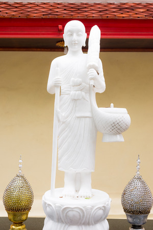White buddha statue in hike mission. Standing buddha statue with monks bowl or alms bowl and umbrella. Thailand. Stock Photo