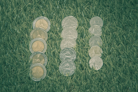 collect: Thai baht coins with grass in background, Thai currency for exchange, save and invest.