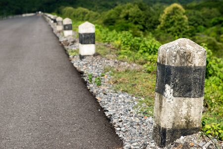 Line of stone bollards at side of asphalt road