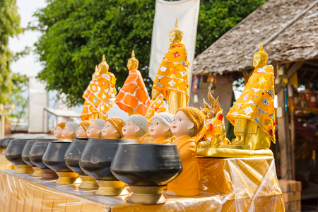 Buddha statues on table with alms bowls Stock Photo