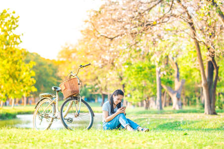 Women sit and listen to music from the smartphone in the garden and bike at sunset,She smiled happily.