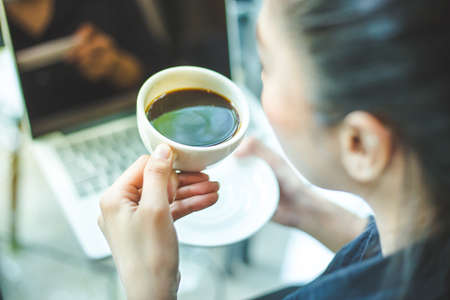 womans hand holding a cup of hot coffee on the office desk,Soft focus