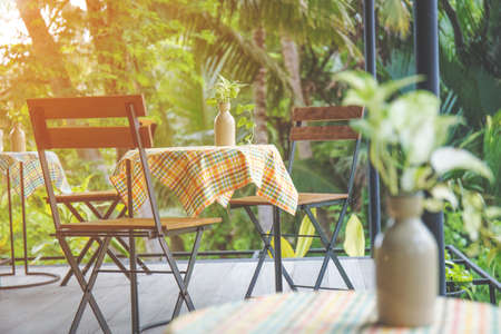 wooden floors: Table and wooden chairs with steel in the coffee shop, table top with colorful tablecloths and vases.at sunset Stock Photo