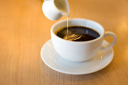 Pouring condensed milk into the coffee.Soft focus