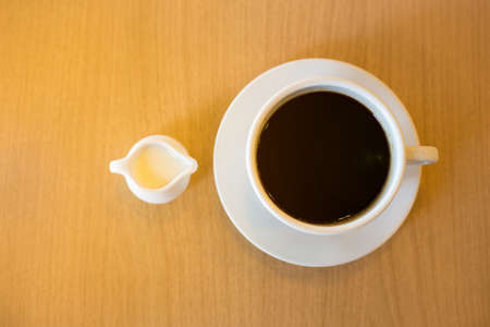 cafe bombon: A cup of condensed milk and coffee on wood background.