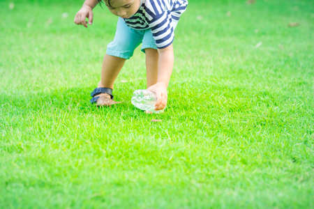 Boy keeps plastic water bottle on grass.The concept teaches children to preserve the environment. Stock Photo