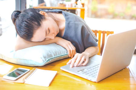 Business woman working in office,She is tired from work and sleeps on a pillow, and her hands are also working at the computer. Stock Photo