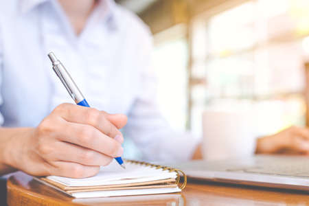 woman hand  using laptop and writing in notepad with a pen. Stock Photo