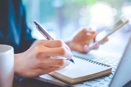 Main de femmes d'affaires travaillent à un ordinateur portable et prendre des notes au bureau.
