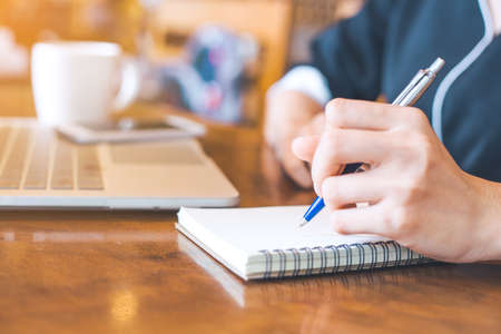 Business woman hand is on a notepad with a pen on a wooden desk in the office.
