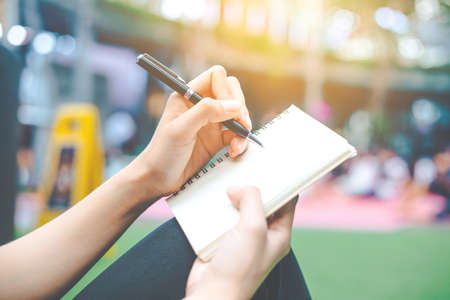 Woman's hand writing on a notepad with a pen. Standard-Bild