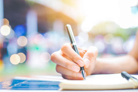 Woman's hand writing on a notepad with a pen on a wooden desk.Background blur backlight