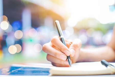 Die Handschrift der Frau auf einem Notizblock mit einem Stift auf einem hölzernen Schreibtisch Hintergrundunschärfebacklight Standard-Bild