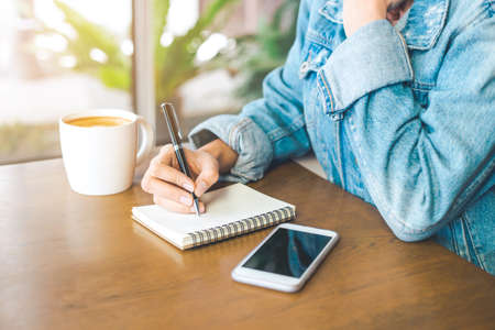 Womans hand writing on a notepad with a pen.And on her wooden desk there is a mobile phone with a cup of coffee.