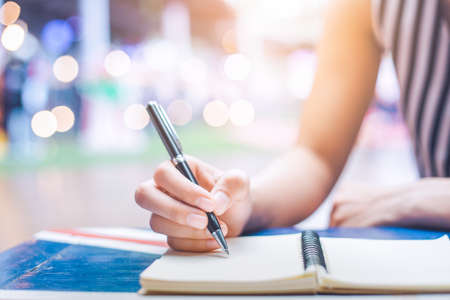 Womans hand writing on a notebook with a pen on a wooden desk.Background blur backlight