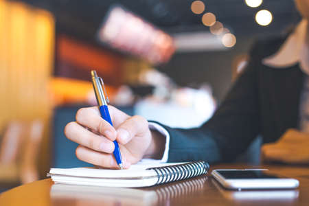 notebook: business woman hand  using mobile phone and writing on notepad with a pen in office. Stock Photo