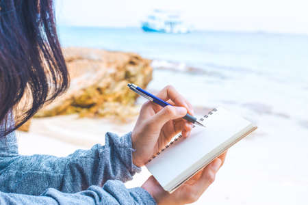 Woman hand writing on a notepad with a pen at the beach.