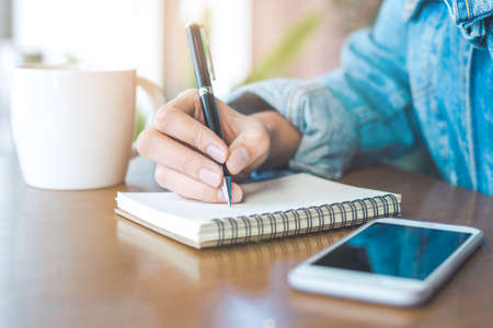 Woman hand writing on a notepad with a pen.And on her wooden desk there is a mobile phone with a cup of coffee. Stock Photo