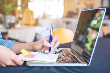 Kobieta ręcznie pisze na notesie piórem w biurze. Na stole są komputery, laptopy i telefony komórkowe. Zdjęcie Seryjne