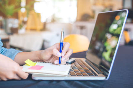 Main de femme écrivant sur un bloc-notes avec un stylo au bureau. Sur la table se trouvent des ordinateurs, des ordinateurs portables et des téléphones portables. Banque d'images