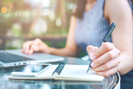 Woman's hand writing on notepad with a pen in the office. On the table are a telephone. Stockfoto