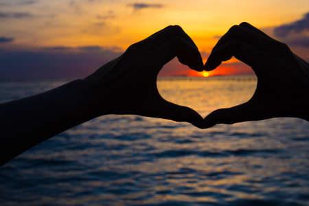 Hands in heart shape at sunset on beach
