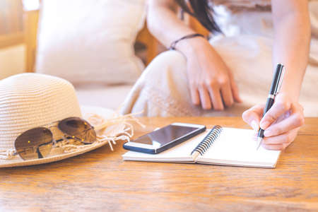 Hipster women in cream dresses are writing on notepad with a pen. On the wooden table there are mobile phones, straw hats and sunglasses.