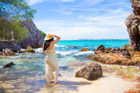 Woman in a cream dress is standing, enjoying the beautiful sea on the beach. Stock Photo