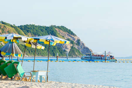 Chair with beach umbrella and boat tour at Koh Lan Thailand. Stock Photo