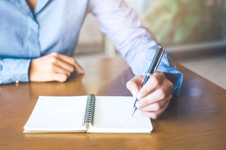 Business woman hand is writing on notepad with pen in office. Stock Photo