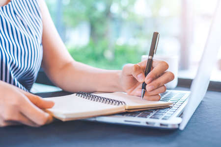 Woman hand writing on notepad with a pen in the office. Stock Photo