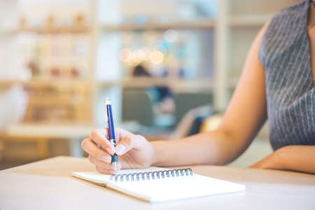 Business woman hand is writing on a note pad with a pen. Stock Photo